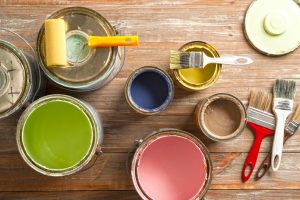 Paint cans, paint roller, and brushes on the old wooden background.
